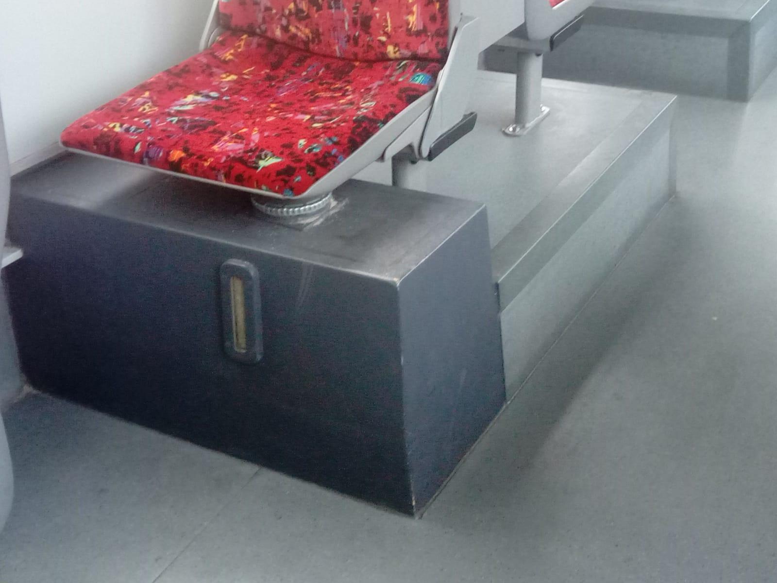Sandbehälter unter einem Fahrgastsitz.